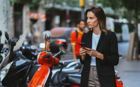 Photo pour Serious girl in a black jacket uses app in smartphone to rent and pay moped to travel around city,  business woman looks at mobile phone screen and plans ride on scooter to get around city quickly - image libre de droit