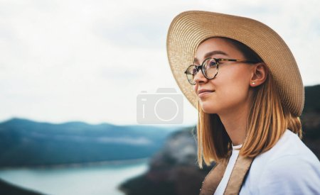Photo for Portrait of cute young blonde in straw summer hat and trendy glasses on background natural landscape and blue sky, empty space for your design - Royalty Free Image