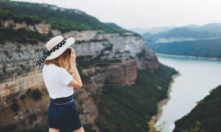 Photo pour Jeune fille blonde en chapeau d'été prend des photos de panorama horizin paysage sur caméra rétro pendant le voyage sur les montagnes en plein air, touriste hipster jouit hobby de photographier belle nature espagne en vacances - image libre de droit