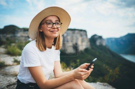 Photo pour Femme touristique souriante dans des lunettes hipster et chapeau à l'aide d'un smartphone et de détente tout en marchant sur les sommets des montagnes, jeune fille blonde voyageur avec mobile randonnée été en plein air bénéficie de loisirs sur la nature - image libre de droit