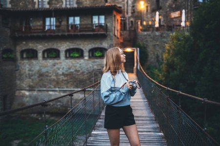 Photo pour Fille touristique se tient sur le pont suspendu marche vieille ville historique et tenir dans les mains appareil photo rétro, jeune femme profite week-end vacances en été utilise appareil photo prend des photos sur fond soirée architecture historique - image libre de droit