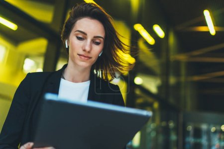 Photo for Successful female banker using tablet and wireless earphones outdoors near office background yellow neon lights, portrait young woman professional manager working on touch pad near skyscraper in evening city - Royalty Free Image