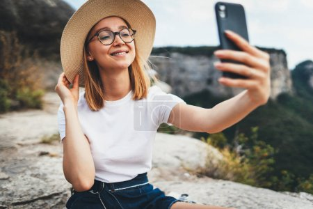 Photo for Smiling woman traveler in summer hat calling by video internet on smartphone leisure on top of mountain landscape, fun female tourist takes photo selfie on mobile phone on background of nature outdoors - Royalty Free Image