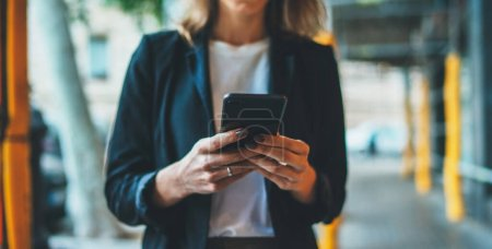 Photo pour Close-up of women's hands writing message in mobile phone, businesswoman checks email in smartphone while walking around the city - image libre de droit