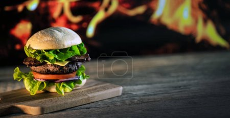 Photo for Fresh tasty cheeseburger on wooden board, fast food concept - Royalty Free Image