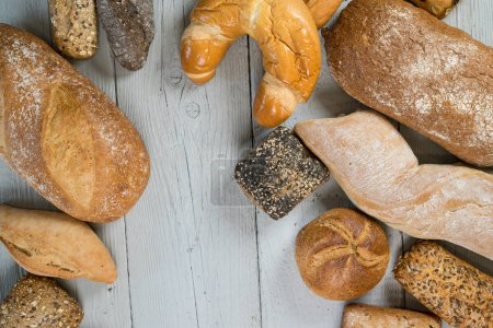 Photo for Variety of delicious loaves of bread on wooden table - Royalty Free Image