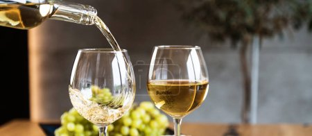 Photo for Closeup of pouring white wine in restaurant - Royalty Free Image