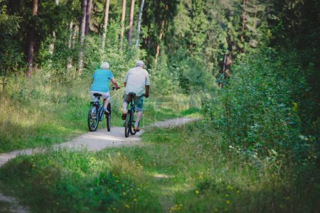 Photo for Active senior couple riding bikes in nature, active retirement - Royalty Free Image