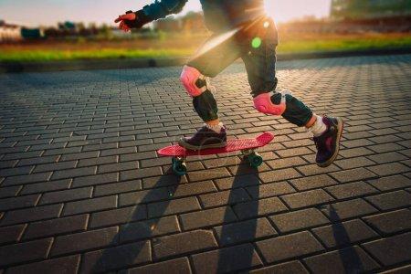 Photo for Little girl skateboarding in sunset city, kid exercise outdoors - Royalty Free Image