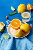 """Постер, картина, фотообои """"апельсин ломтиками лимона и Лайма на синем фоне деревянные, лимонада ингредиентов концепции"""""""