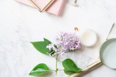 feminine workspace mock-up with card and notebook with lilac flowers and magnifying glass on marble background