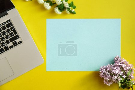 Photo for Beautiful flowers and blue empty card with laptop on yellow background, concept of spring female blogger workspace - Royalty Free Image