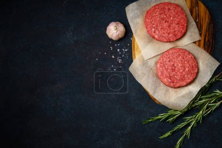wooden cutting board with raw minced beef patties with rosemary twigs and garlic on dark blue background