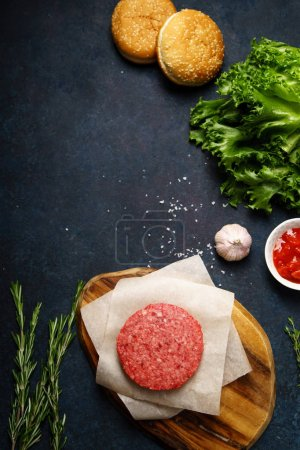 classical american burger ingredients on dark blue background, concept of cooking burger