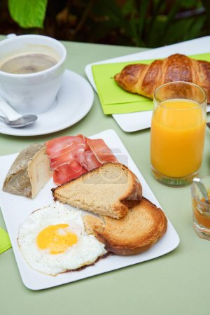 Photo for French breakfast on table in small cafe with inner garden. with coffee cups and croissant with orange juice and fried egg with toasts on green table - Royalty Free Image