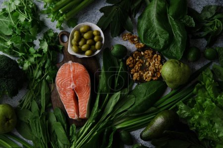 Photo for Fresh healthy vegetables with greens and fruits with walnuts and raw salmon steak on grey background, Healthy food ingredients concept - Royalty Free Image