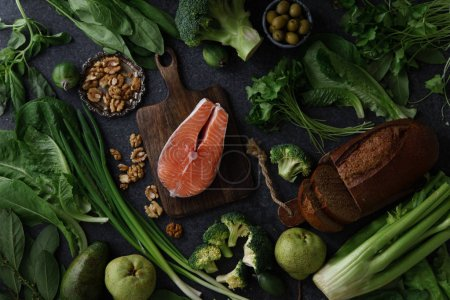 Photo for Fresh healthy food composition of vegetables with greens and fruits with raw salmon steak and walnuts with bread - Royalty Free Image