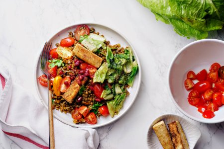 Photo for Vegetarian lentil salad with fried cheese and greens with fresh vegetables in bowl - Royalty Free Image