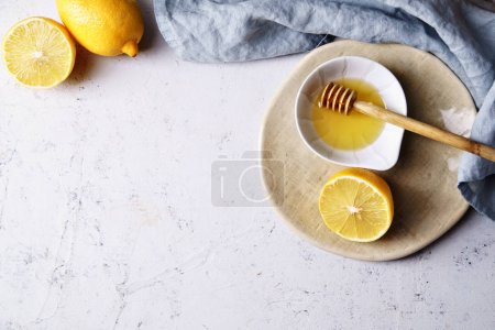 Top view of lemons and honey in bowl on wooden cutting boars with textile, homemade cosmetics concept