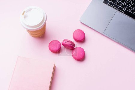 Photo for Female blogger workplace with laptop and coffee to go cup with notepad and macaroons on pink background. Top view - Royalty Free Image