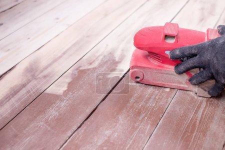 Wood floor polishing maintenance work by grinding machine. Mens hands with gloves make repairs at home. Grinding machine with a wooden floor.Copy space. restoration of the floor.