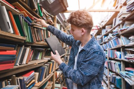 Handsome young man looking for books on bookshelves of an old library. Portrait of a student who browses books from public library shelves.