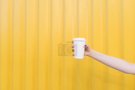 Photo for A man is holding a brown paper cup - Royalty Free Image