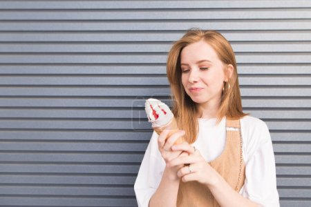 attractive redhead girl standing on a gray background with gusto and looks at an ice cream in hand. Portrait of a pretty girl looking at delicious ice cream. Copyspace