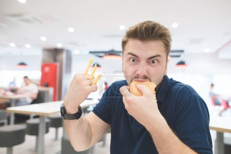 Photo for Portrait of a funny emotional man with French fries instead of fingers who eats a burger in a fast-food restaurant and looks at the camera. Fast Food Concept. - Royalty Free Image