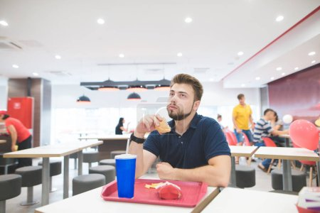Photo for Student with a beard sits at the table with a fast food tray in a fast-food restaurant with a burger in his hands and eats. Man dishes with delicious fast food. Fast tasty food concept. - Royalty Free Image