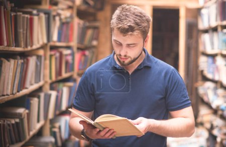 Portrait of a man reading a book standing in a public old library. Book search in the library. Self-education A student is looking for literature.