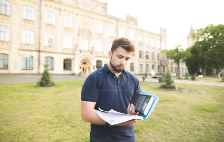 Frustrated man with a beard stands against the background of a building with books in his hands. Sad student standing against the background of the university building and looking at the notebook