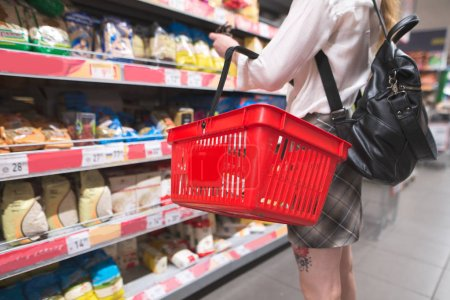 Stylish woman with a red shopping basket in her hands makes purchases in a supermarket. Girl chooses food at the store. Shopping in a supermarket concept.