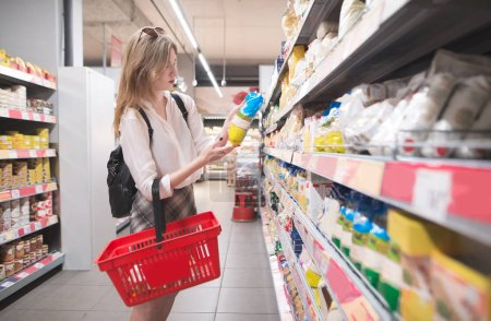 Photo for Stylish young girl standing in a grocery supermarket in her arms and reading a label. Female buyer selects products in a supermarket. - Royalty Free Image