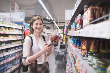 Happy, stylish girl standing in a ketchup bottle in the hands of a supermarket and looking into the camera. Happy buyer makes purchases in the supermarket.