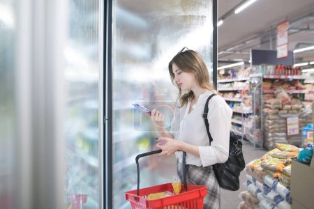 Attractive young woman stands at the refrigerator in the store with frozen food in his hands. Young girl with a red basket buys frozen food at a supermarket.
