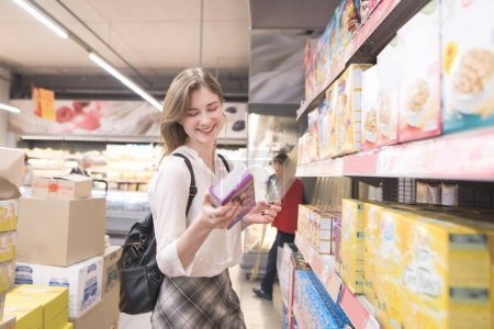 Happy, attractive woman is in the supermarket with a pack of quick breakfasts in her hands and smiles. Smiling girl buys flakes in a supermarket
