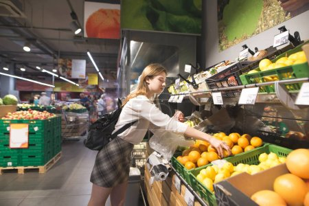Stylish young woman buys fruit in a supermarket. Girl is collecting oranges in a package during a supermarket shopping. Buyer buys the fruit in the store