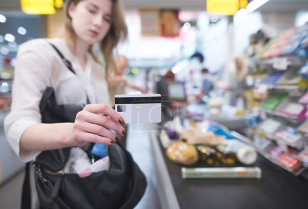 Woman is at the supermarket's cash desk and shows a credit card. Payment by credit card at the store. Focus on the hand with a card.