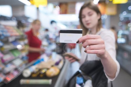 Woman is at the supermarket's cash desk and shows a card in the camera. Payment by credit card at a supermarket. Card in the hands of a woman close-up on the background of the supermarket cash desk