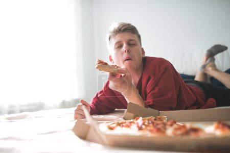Happy young man lying home on a sofa with a box of pizza, bites a piece of pizza with his eyes closed and gets pleasure. Teen is home to the bed and eats a delicious pizza. Copyspace