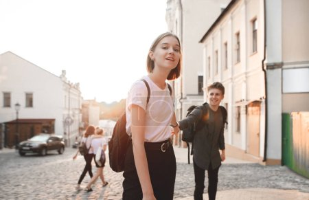 Attractive girl holds a young man by the hand and goes with him along the street of the old town on the background of the sunset. Happy man follows a girl on the background of the sunset. Follow me.