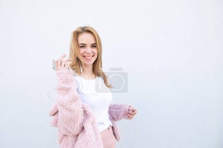 Happy, trendy girl in a teenager in cute clothes, poses with headphones and a smartphone on the background of a white wall, looks camera and smiles. Cute young woman. Copyspace