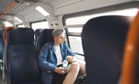 Photo pour Un jeune homme coiffé d'une casquette et une bouteille d'eau à la main se déplace en train et regarde par la fenêtre. Un étudiant prend le train . - image libre de droit