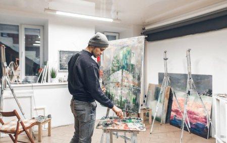 Photo pour Portrait d'un élève d'artiste, dessinant une peinture dans un atelier. Jeune peintre peint une nouvelle peinture à l'huile dans son propre atelier confortable. Travail créatif . - image libre de droit