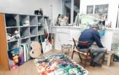 """Постер, картина, фотообои """"Палитра краски и кисти на фоне художественной студии и художник рисует картину. Художник рисует картину в художественную студию, на переднем плане палитру кистей"""""""