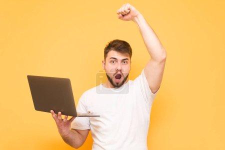 Photo pour Homme adulte avec un ordinateur portable dans ses mains a gagné, se réjouit de la victoire avec sa main levée, regardant dans la caméra. Homme heureux avec un ordinateur portable isolé sur un fond jaune . - image libre de droit