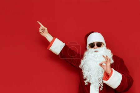 Photo for Cheerful Santa Claus stands on a red background and points his hand to a blank space and with his fingers gesture ok, looks into the camera and smiles. Positive Santa pointing finger at Copyspace - Royalty Free Image