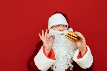 Photo for Cheerful Santa Claus stands on a red background with a burger in his hand, shows his finger the OK sign, looks into the camera and smiles. Man in Santa's suit likes fast food. Harmful food. Christmas - Royalty Free Image