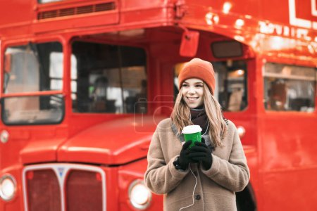 Photo for Portrait of happy girl in warm clothes on a walk on a winter cold day, stands on a background of a red bus with a cup of coffee in her hands, looking away. Christmas concept. - Royalty Free Image